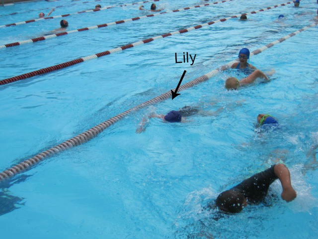 Lily swimming with her team during warm-ups.