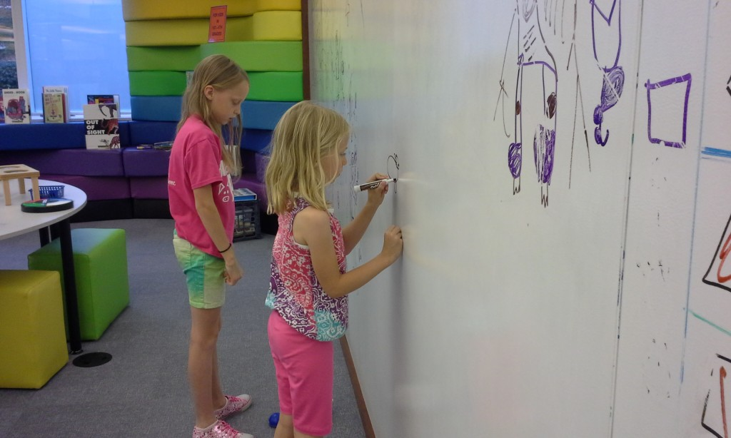 Lily and Emmy coloring on the new white board wall in the Discovery Zone.